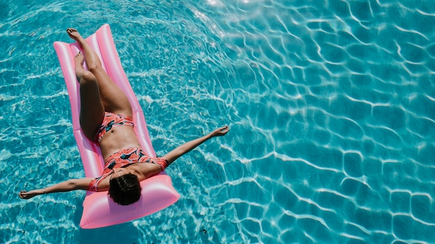 Top view of woman relaxing on mattress in pool
