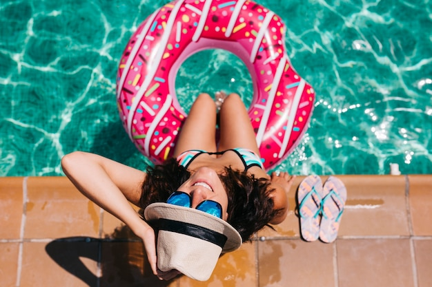Top view of a woman relaxing in the pool with pink donuts in hot sunny day summer holiday idyllic enjoying suntan woman in bikini and a hat holidays and summer lifestyle