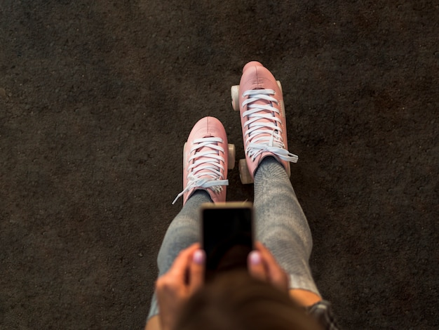 Top view of woman in roller skates holding smartphone