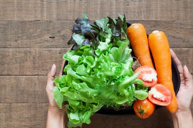 新鮮な野菜のプレートを保持している上から見る女性の手