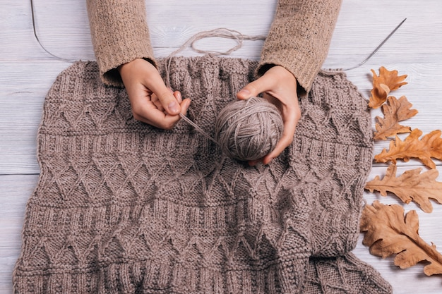 Top view of a woman's hands holding a ball of wool yarn on a table with knitting