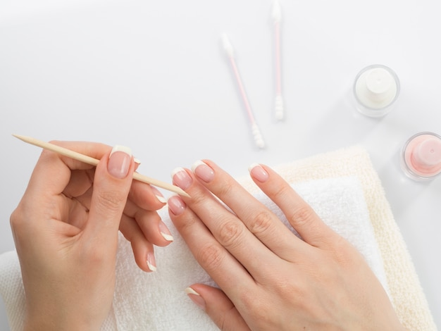 Top view woman's hands using manicure tools