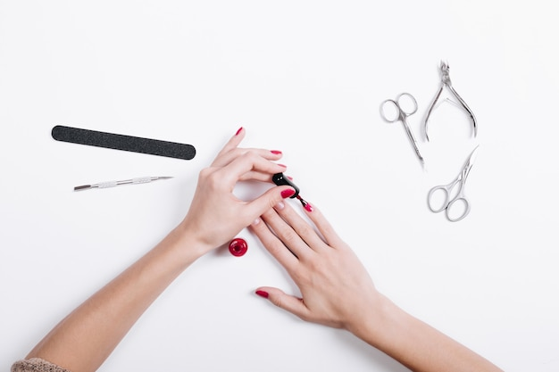 Top view of a woman's hands with red nail polish and manicure tools