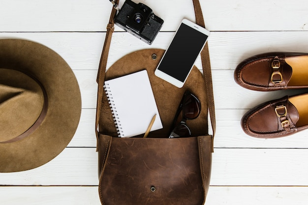 Top view of woman's journalist or traveler accessories on white wooden table background