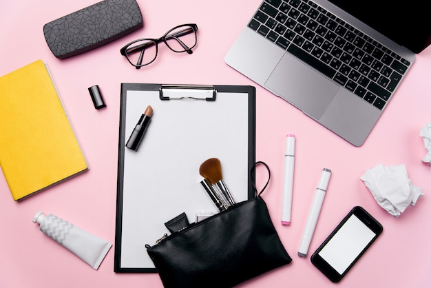 Top view of woman's pink office desk with laptop, phone with white screen, eyeglasses, lipstick, cream, cosmetic bag and crumpled paper balls background.