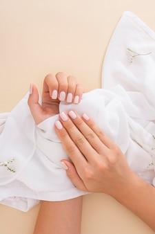 Вид сверху женщина показывает свой маникюр на белой ткани