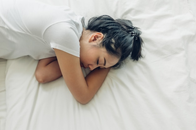 Top view of woman sleeping on her bed with white copy space.