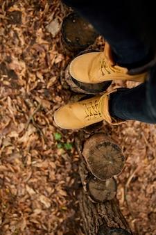 紅葉と木の背景にハイキングマウンテンブーツと立っている上面図の女性