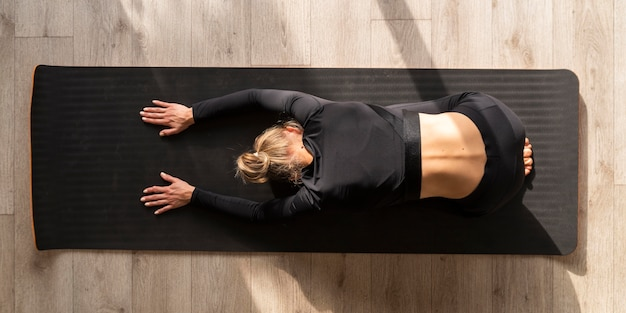 Top view woman stretching on mat