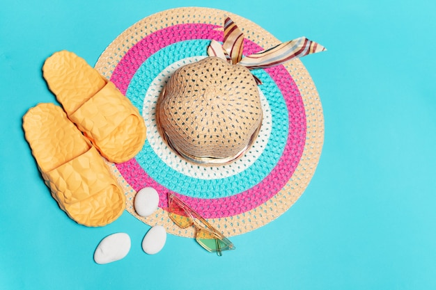 Top view of woman summer hat with yellow slippers near sunglasses and stones  background.