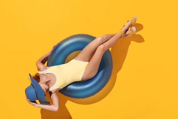 Donna di vista superiore in costume da bagno che si abbronza