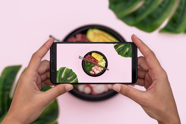 Top view of woman taking picture of tuna poke bowl on pink background