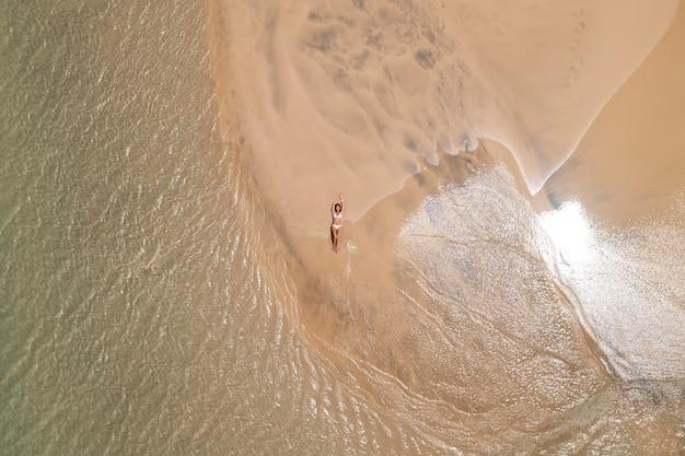 Vista dall'alto donna che si abbronza sulla spiaggia