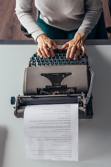 Top view of a woman typing text on a typewriter.