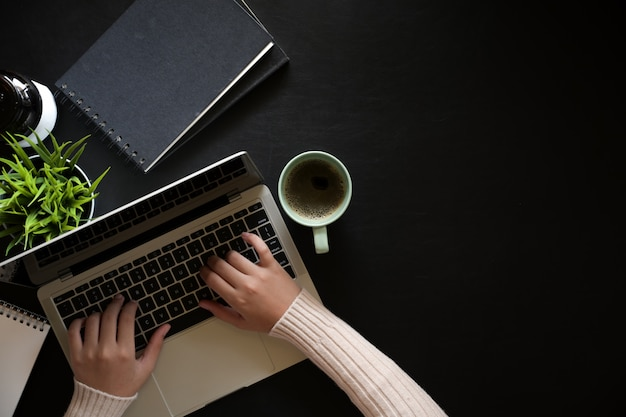 Top view woman using laptop on dark leather workspace desk