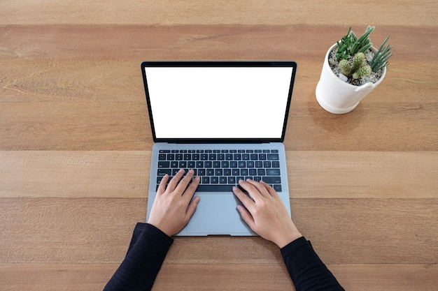 Top view  a woman using and typing on laptop with blank white screen and cactus pot on wooden table background