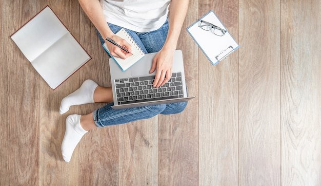 Top view of woman with laptop sitting on the wooden floor at home.