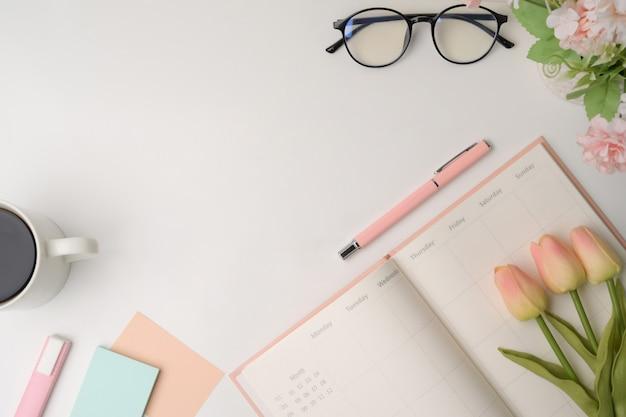 Рабочая область женщины вид сверху с дневником, цветами и очками на белом столе.