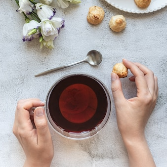 Top view of a womans hands with a cup of tea cookies and flowers