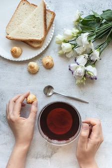 Top view of a womans hands with a cup of tea cookies toasted bread and flowers