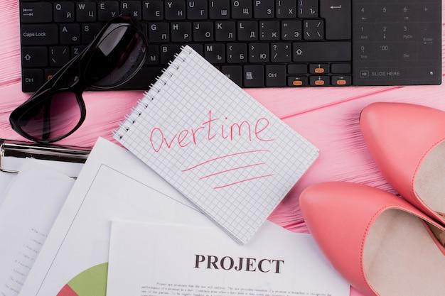 ピンクの木製テーブルにさまざまな紙のキーボードのメモ帳とトップビューの女性のテーブルデスク