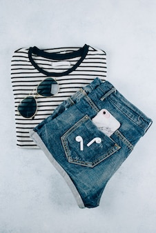 Top view of  women's clothing striped t-shirt, denim shorts and accessories eadphones, smartphone.