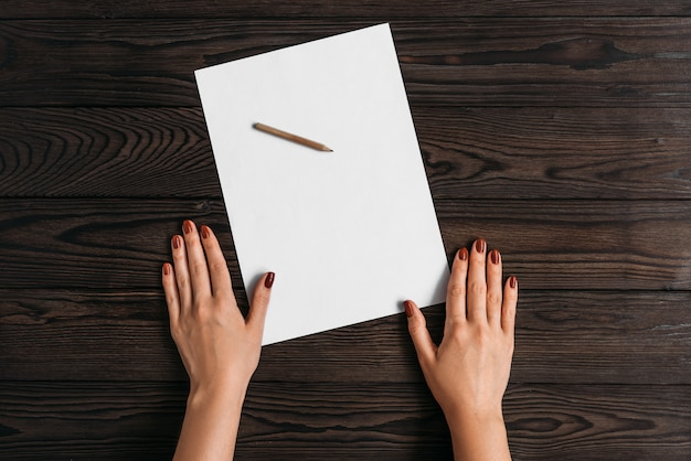 Top view of women's hands, ready to write something on an empty piece of paper