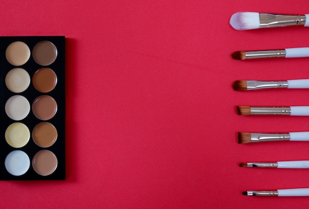 Top view of women's cosmetic on red background.