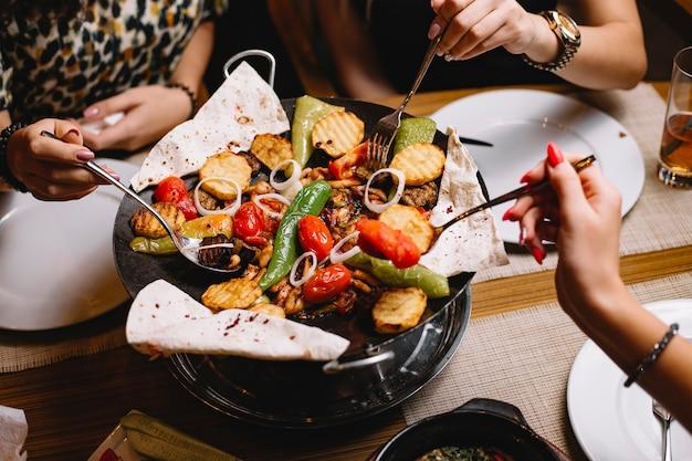 Le donne della vista superiore mangiano un piatto tradizionale azero di salvia di pollo con verdure patate e pane pita
