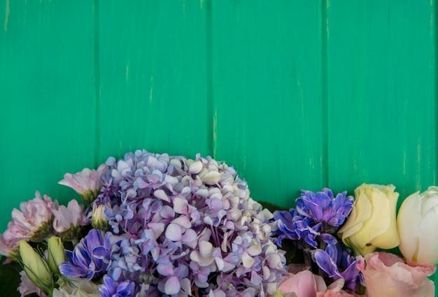 Vista dall'alto di meravigliosi fiori colorati come la margherita di gardenzia rosa su uno sfondo di legno verde con spazio di copia