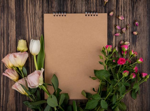 Vista dall'alto di meravigliose rose rosa con boccioli di rosa e tulipano su uno sfondo di legno con spazio di copia