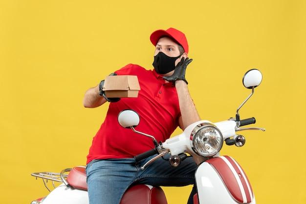 Vista dall'alto del ragazzo delle consegne chiedendo che indossa guanti uniformi e cappello in maschera medica che si siede sullo scooter che mostra l'ordine