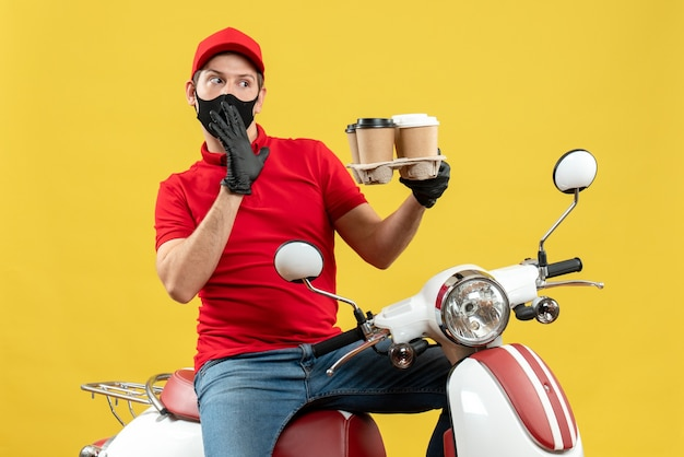 Top view of wondering delivery man wearing uniform and hat gloves in medical mask sitting on scooter showing orders