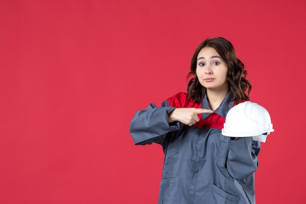Top view of wondering female architect holding hard hat and pointing it on isolated red background