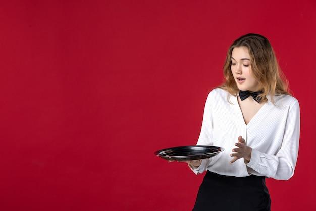 Vista dall'alto di chiedersi il papillon femminile del server sul collo e tenere il vassoio sul muro rosso