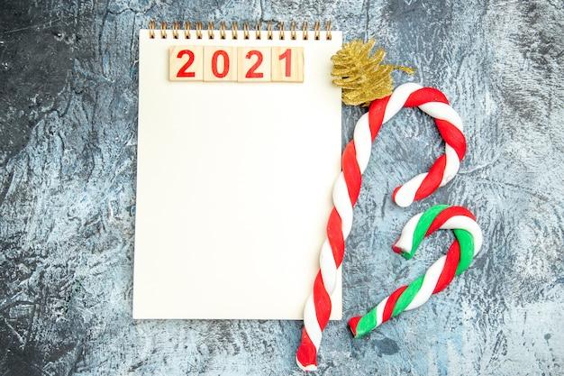 灰色の背景にノートブッククリスマスキャンディーのトップビューウッドブロック