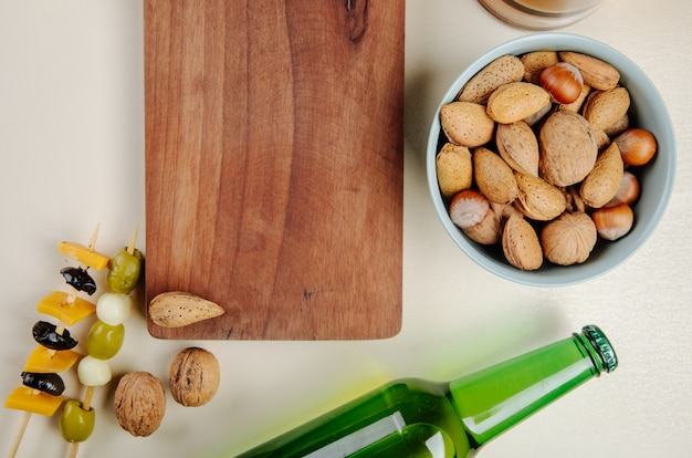 Top view of a wood board and mix of nuts in a bowl pickled olives and bottle of beer on white
