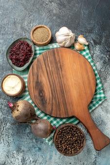 灰色のテーブルの上のボウルにんにくビートの上面図木製サービングボードスパイス