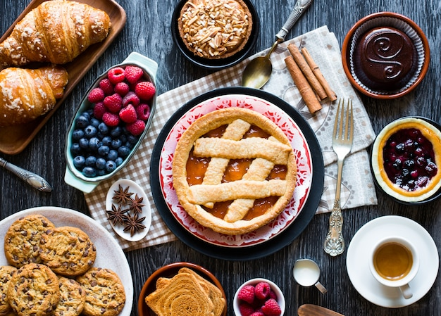 Top view of a wood table full of cakes, fruits, coffee, biscuits, spices and more