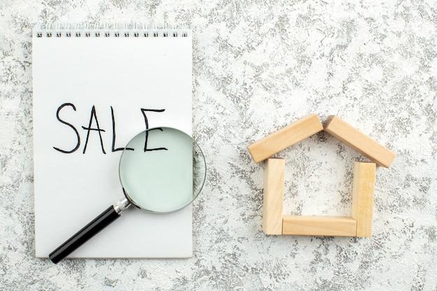 회색 테이블 여유 공간에 노트북에 쓰여진 상위 뷰 나무 블록 집 모양 판매