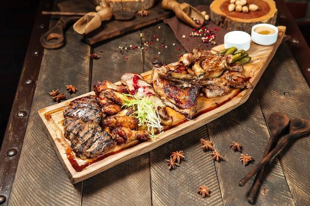 Деревянная доска вид сверху с ассорти жареного мяса