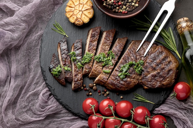 Top view wooden board with tasty cooked meat