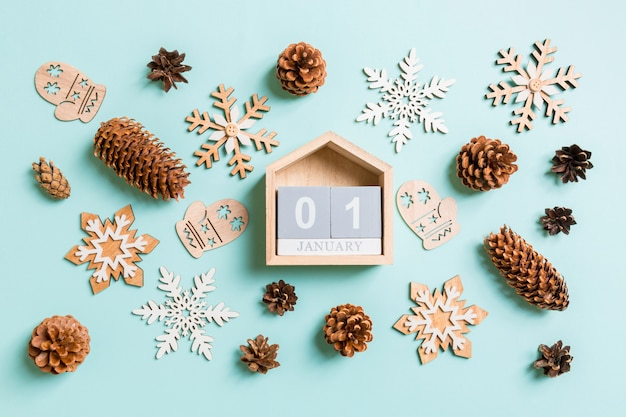 Top view of wooden calendar, holiday toys and decorations on blue christmas.
