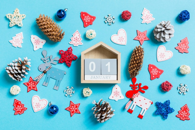 Top view of wooden calendar surrounded with new year toys and decorations on blue.