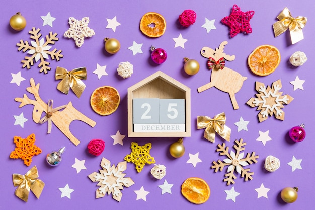 Top view of wooden calendar surrounded with new year toys and decorations on purple.