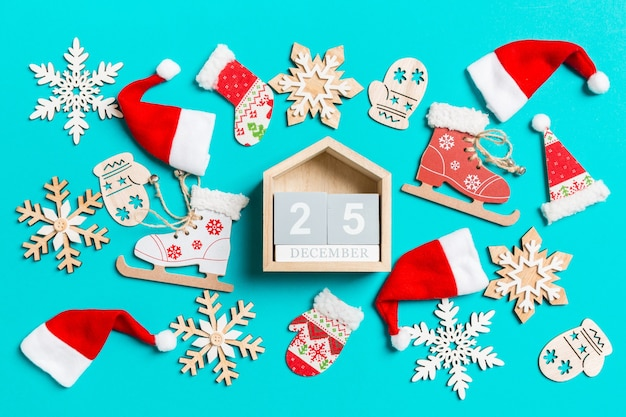 Top view of wooden calendar with christmas decorations and santa hats on blue background. the twenty fifth of december. happy holiday concept.
