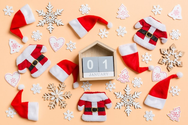 Top view of wooden calendar with christmas decorations and santa hats on orange.