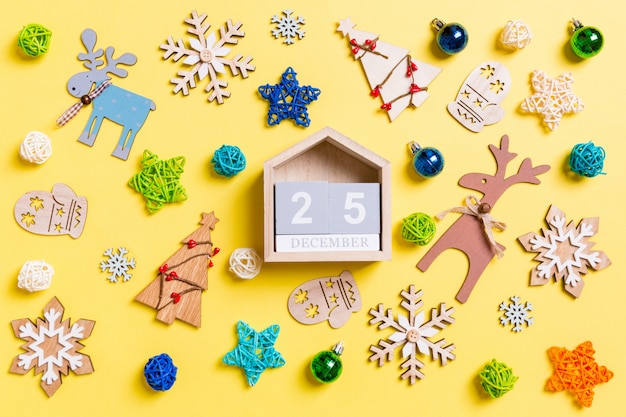 Top view of wooden calendar on yellow with new year toys and decorations.