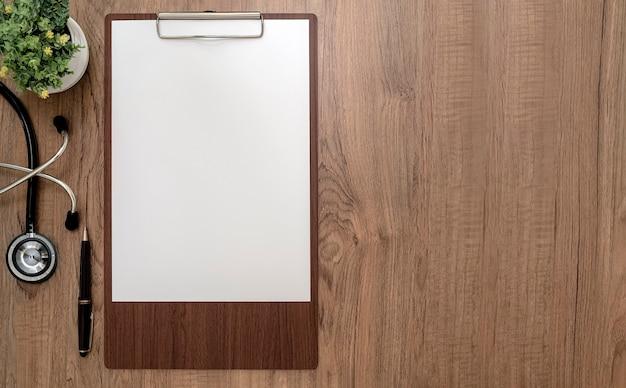 Вид сверху деревянный буфер обмена с пустой бумагой формата а4 и стетоскопом на деревянном столе