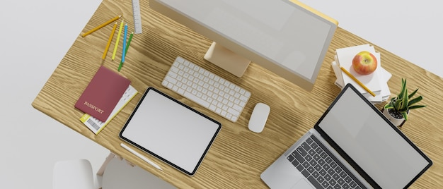 Top view of wooden computer desk with computer tablet and laptop blank screen mockup and decor